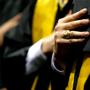 Hand with Aggie ring, holding graduation cap over robes